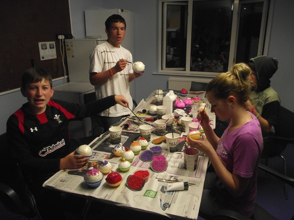 Young people painting cupcake props