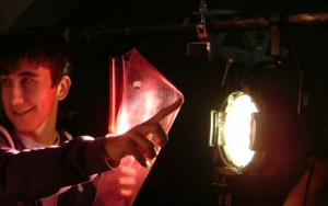 Young person inserting lighting gel to theatre light