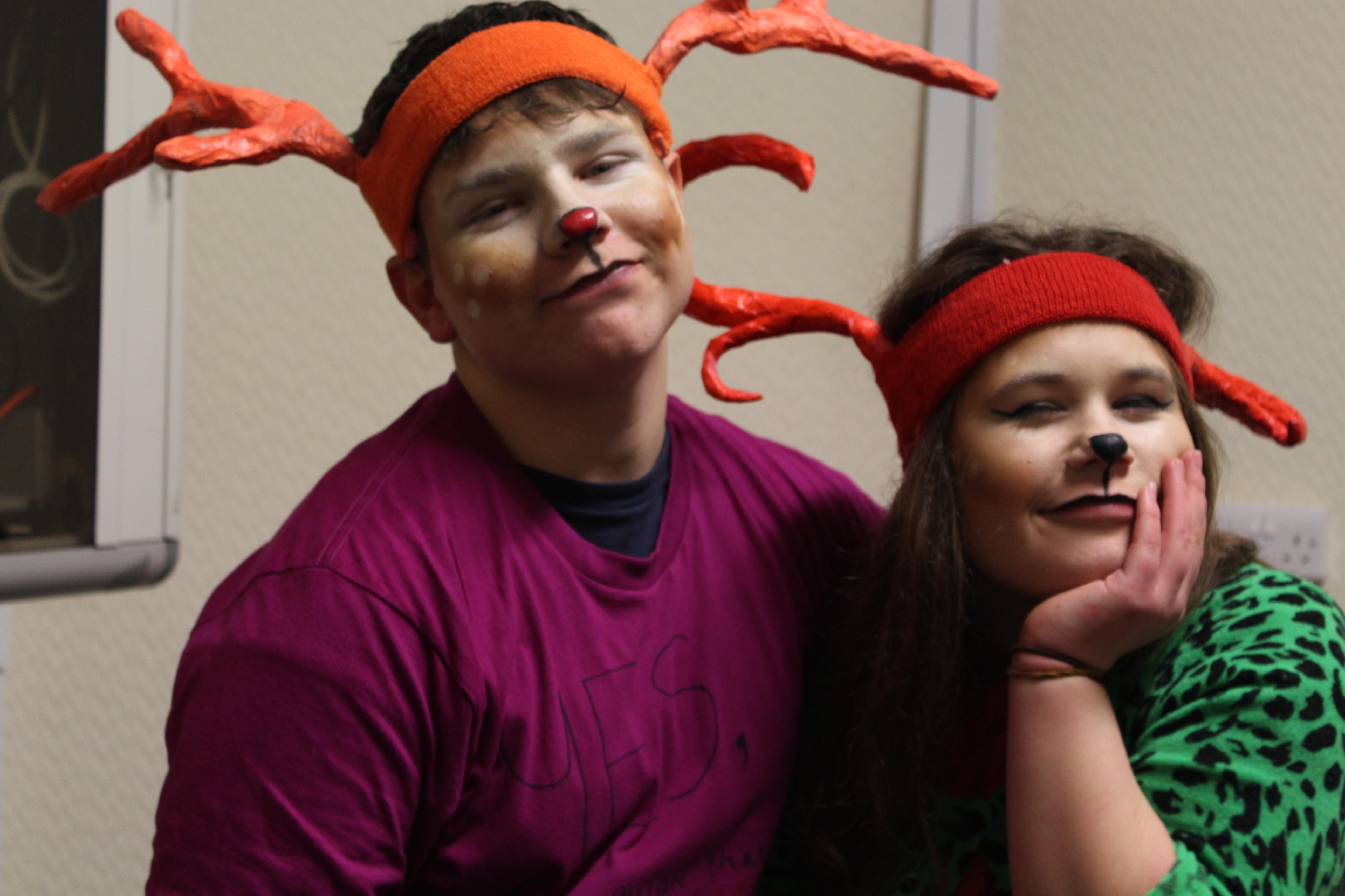 2 young people wearing reindeer antlers