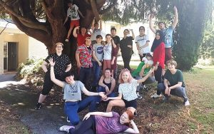 a group of young people outside under a tree celebrating