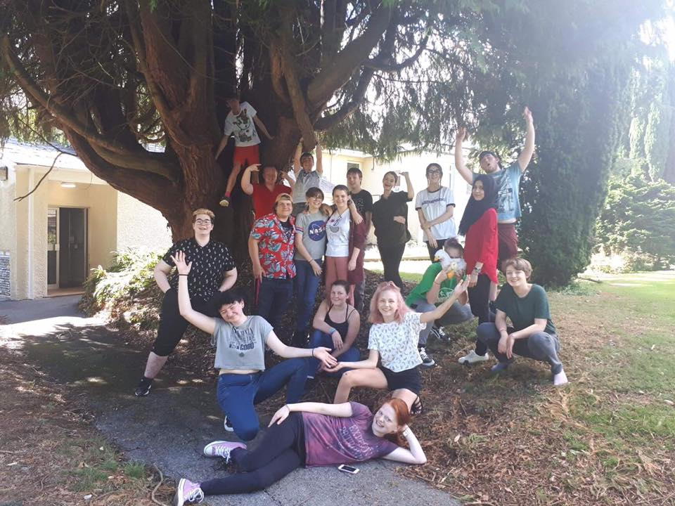 a group of young people outside under a tree celebrating the end of training