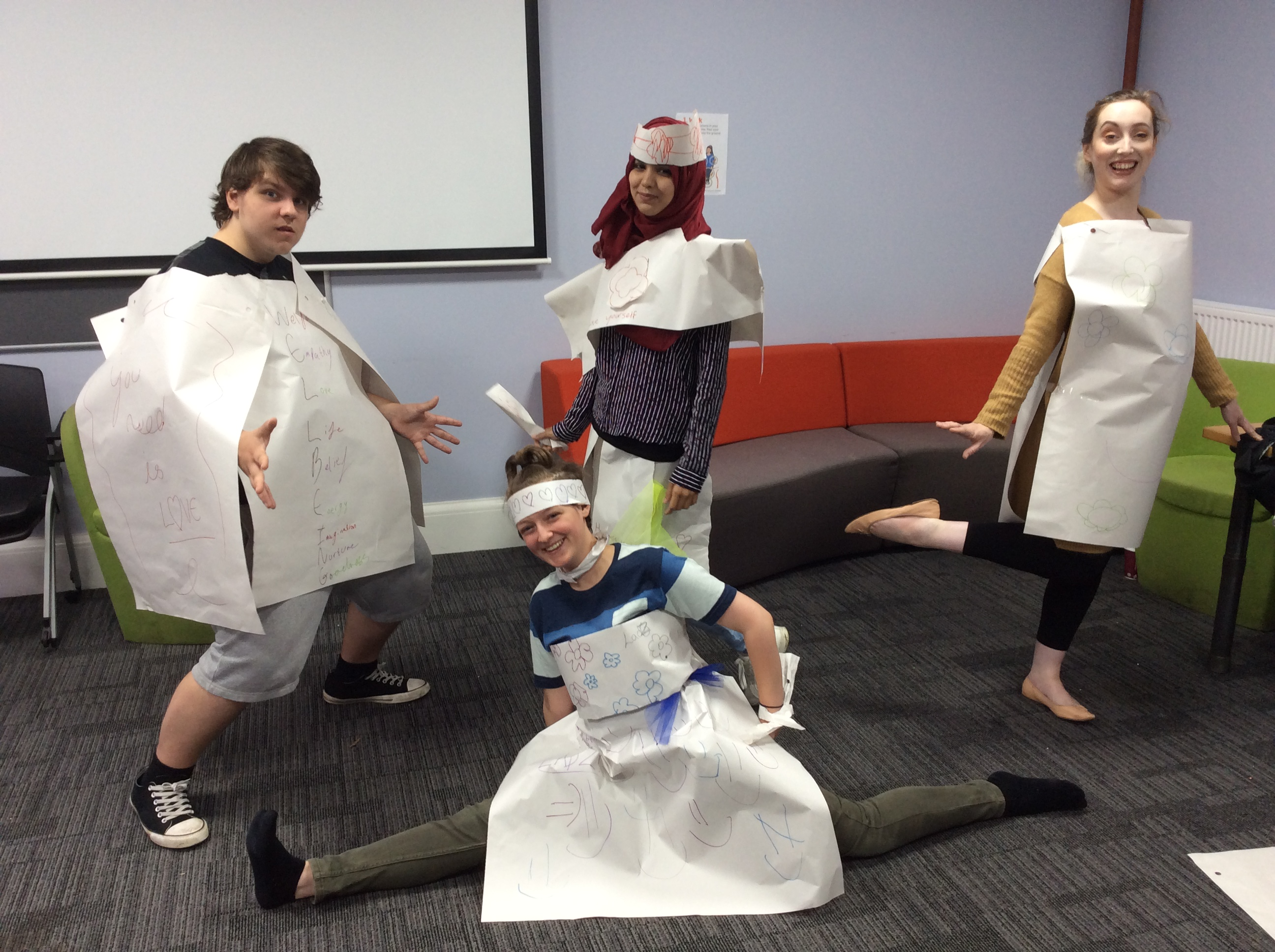 four people dressed in paper costumes
