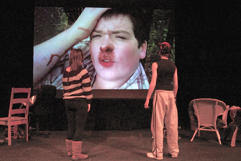 Patrick and Vicky observe Welsh Ninja, unmasked and bloodied, on a big screen
